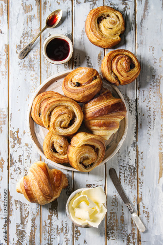 Valokuva Variety of homemade puff pastry buns cinnamon rolls and croissant served with jam, butter as breakfast over white plank wooden background
