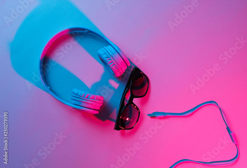 Poster Magasin de musique Sunglasses with headphones. Retro wave, blue pink neon light, ultraviolet. Top view, minimalism