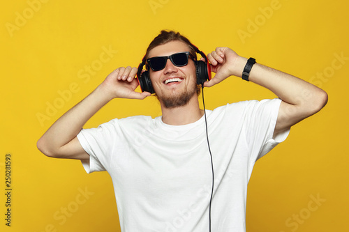 Foto  Close up portrait of a cheerful young caucasian male with sunglasses listening to music with headphones isolated over yellow background