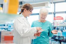 Pharmacist Servicing Senior Customer In Her Pharmacy
