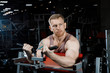 Strong man pumping biceps in gym