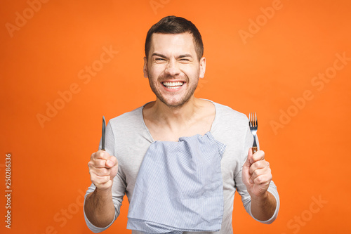 Fotografie, Obraz Young hungry crazy man holding a fork and a knife