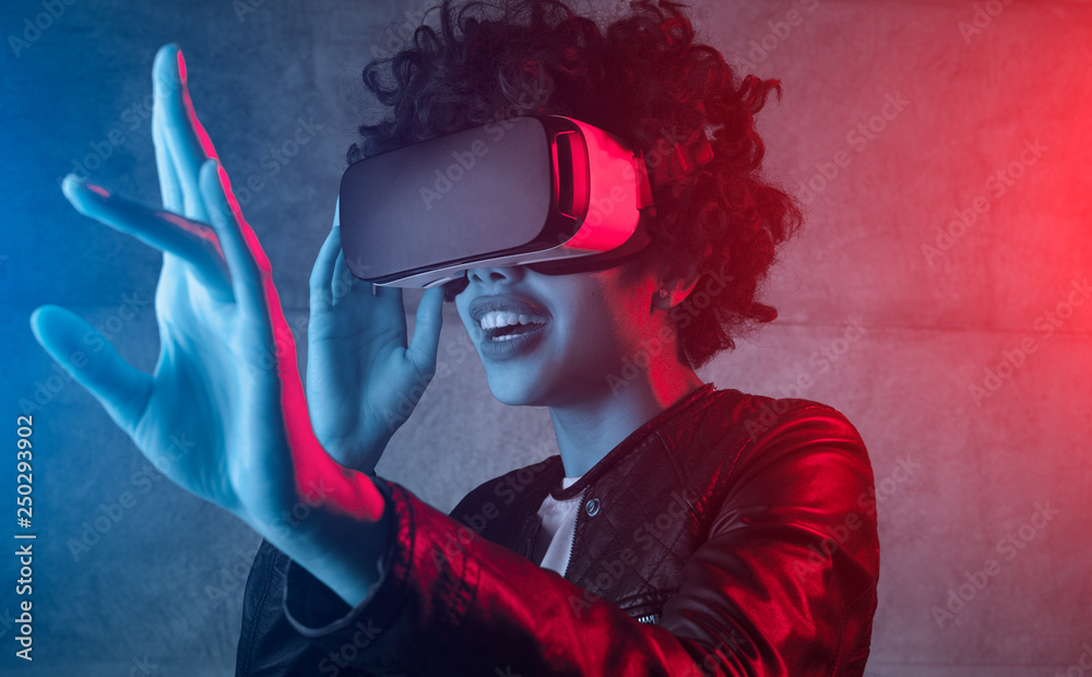 Fototapeta Excited girl wearing VR headset in neon light