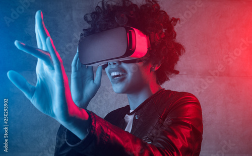 Leinwand Poster Excited girl wearing VR headset in neon light