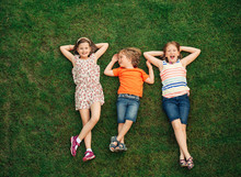 Happy Children Having Fun Outdoors. Kids Playing In Summer Park. Little Boy And Two Girls Lying On Green Fresh Grass