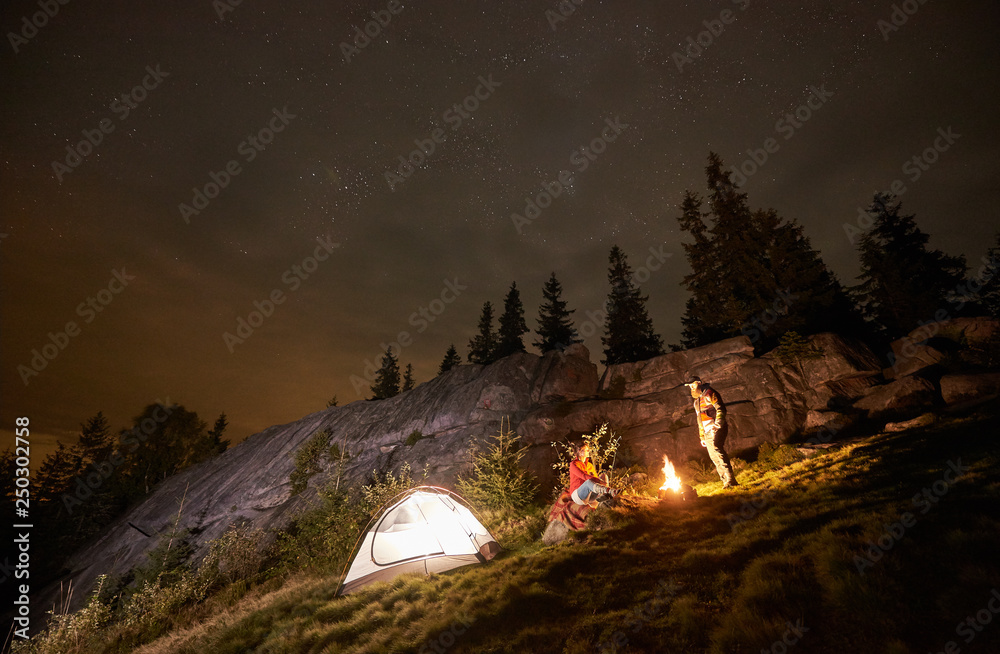 Fototapeta Night summer camping in the mountains. Happy couple travellers having a rest together beside campfire and illuminated tourist tent. On background big boulder, forest and beautiful night starry sky. - obraz na płótnie