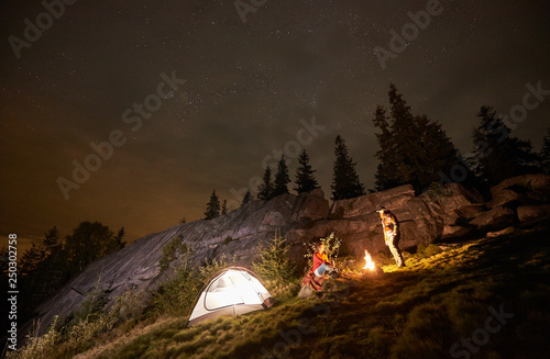 Fototapeta Night summer camping in the mountains. Happy couple travellers having a rest together beside campfire and illuminated tourist tent. On background big boulder, forest and beautiful night starry sky. obraz na płótnie