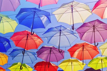 Colorful umbrellas on the sky background, toned.