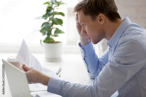 Obraz Man reading notification from bank about unpaid debt - fototapety do salonu