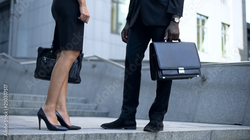 Photo Managers talking near office, view on leather shoes and briefcase business style