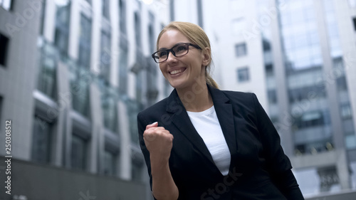 Business woman showing yes gesture, rejoices at promotion and successful career Wallpaper Mural
