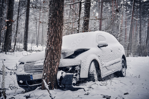Foto  Front view of the car got into a skid and crashed into a tree on a snowy road