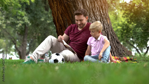 Photo Father reading book with son in park, preparing homework together, parenting