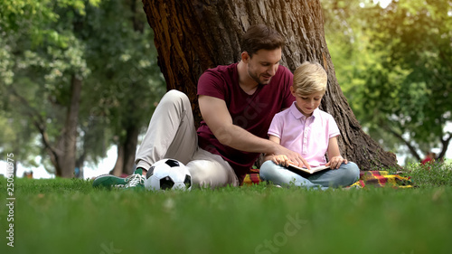Father and son reading book in park, man encourages boy to knowledge, family Wallpaper Mural
