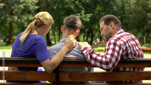 Canvas Print Caring mother and dad supporting sad teen son sitting on bench in park, crisis