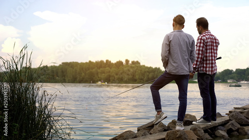 Fotografiet  Father and teenager son fishing together, relaxing near lake, favorite hobby