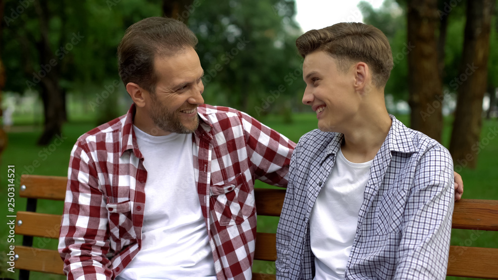 Fototapety, obrazy: Teenage son talking with father on bench, telling secrets and smiling, trust