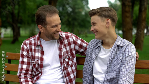Fotografía  Teenage son talking with father on bench, telling secrets and smiling, trust