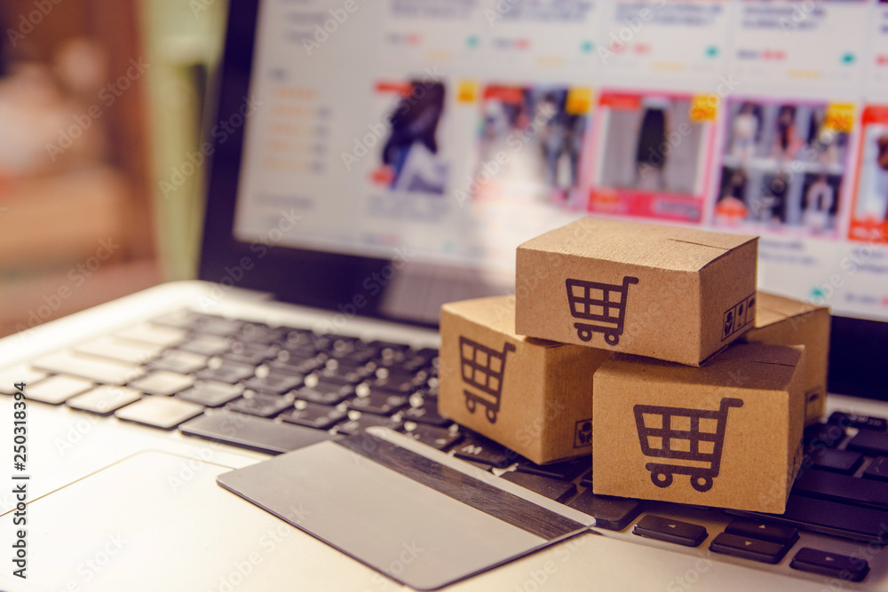 Fototapeta Shopping online concept - Shopping service on The online web. with payment by credit card and offers home delivery. parcel or Paper cartons with a shopping cart logo on a laptop keyboard