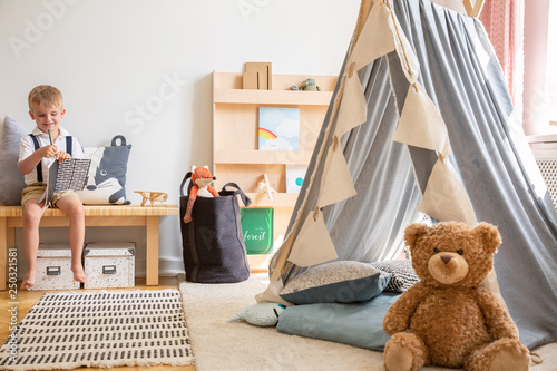 Teddy bear next to grey scandinavian tent in stylish boy's bedroom with furniture made from natural materials, real photo with copy space on the white wall