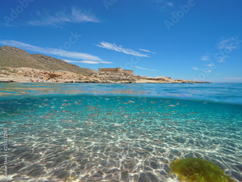 Spain Mediterranean coast with a castle and school of fish (bogue) with sand underwater sea, el Playazo de Rodalquilar, Almeria, Andalusia, split view half over and under water