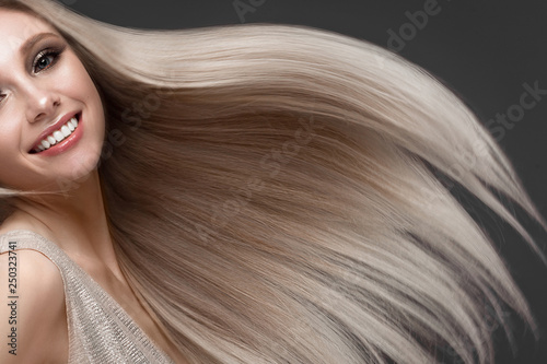 Fotomural Beautiful blond girl in move with a perfectly smooth hair, and classic make-up