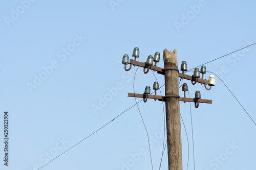 Fotografie, Obraz  Old electric  wooden pole with glass and ceramic insulators and electric wires against blue sky