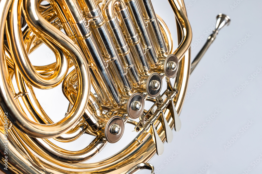 Fototapeta French horn on a white table. Beautiful polished musical instrument.