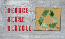 Recycle Symbol Made Of Recycled Materials On Cardboard Square With Reduce Reuse Recycle In Red Text On Old Wall