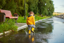 Small Boy In Yellow Raincoat Playing In Puddles