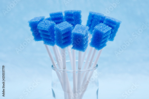 Fotografie, Obraz  Untreated disposable oral swabs on blue under pad.