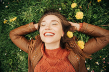 Close Up Portrait Of Young Beautiful Woman With Brown Hair Lying On Grass