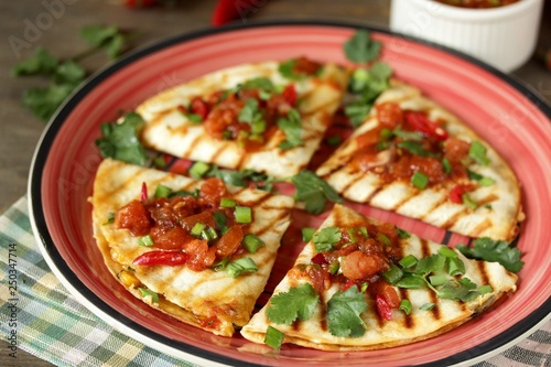 Quesadilla grill with spicy salsa with chili pepper. Mexican traditional food, wheat tortillas.
