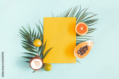 Summer composition. Tropical palm leaves, fruits, yellow paper blank on pastel blue background. Summer concept. Flat lay, top view, copy space - 250358795