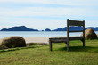Empty wooden bench on the beach, looking into the wide and endless sea