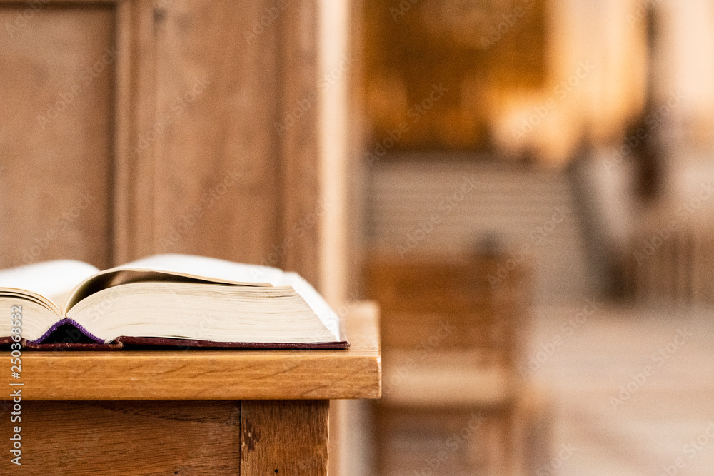 Fototapety, obrazy: Holy book on a table in front of the altar of the church and with a view to the great big churchroom