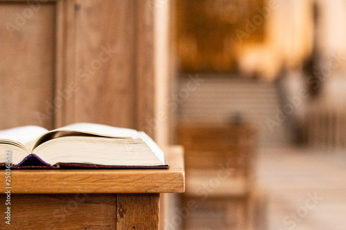 Obraz na plátně  Holy book on a table in front of the altar of the church and with a view to the