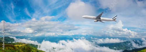 Poster Avion à Moteur Panorama Photo An airplane flying in the blue sky. passenger plane flies highly over clouds of aerosphere. airplane flying in a clear pale blue sky. An airplane taking off at airport.