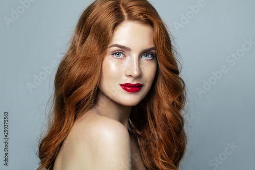Fotografie, Obraz  Pretty red haired woman studio portrait. Redhead girl smiling