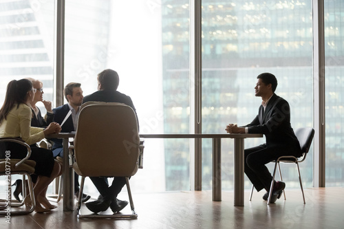 Fototapeta  Hr team interviewing african candidate sitting at table in office