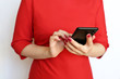Leinwanddruck Bild - Slim girl in red dress with smartphone in manicured hands on white background. Concept of business woman, online communication, text messaging