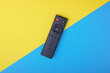 canvas print picture - Remote control TV or radio on blue  and yellow background with selective focus and crop fragment