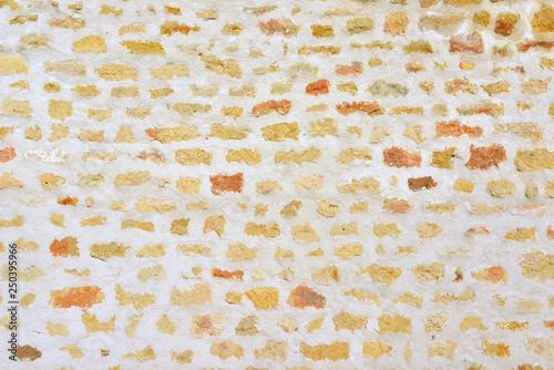 Fototapeta Mur de pierres jaunes et orangées incrustées avec enduit blanc
