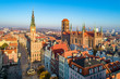 Poland. Gdansk Old City skyline with medieval Gothic Saint Mary Cathedral, city hall with clock tower, Dluga street, Neptune statue with fountain, Artus Court, Aerial view in sunrise light