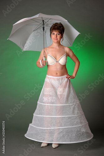 Fotografía girl in a petticoat with an umbrella on a green background