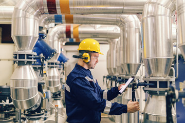 Profile of young Caucasian worker tightening the valve and using tablet while standing in heating plant.