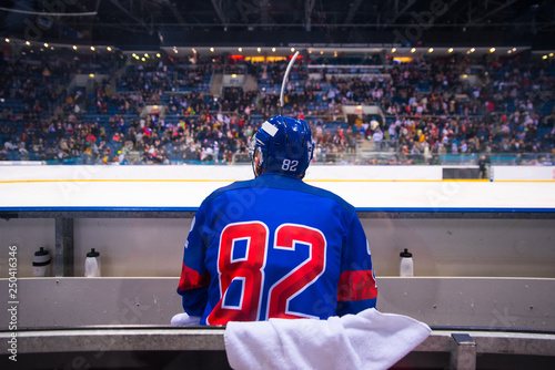 hockey player sitting on the bench, stadium and crowd in background Fototapeta