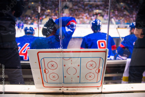Fotografía  Hockey players sitting on the bench. Tactic board in foreground