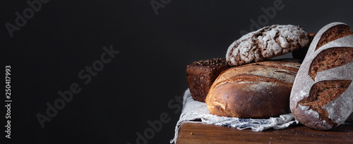 Recess Fitting Bread Loafs Of Traditional And Natural Bread on a wooden table with linen towel. Assortment of artisanal bread. Healthy food concept. Panoramic frame with free space for input text.