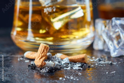 Cadres-photo bureau Bar Cigarette butt with glass of whiskey behind on black rustic background